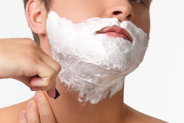 T字カミソリで髭剃りをする男性